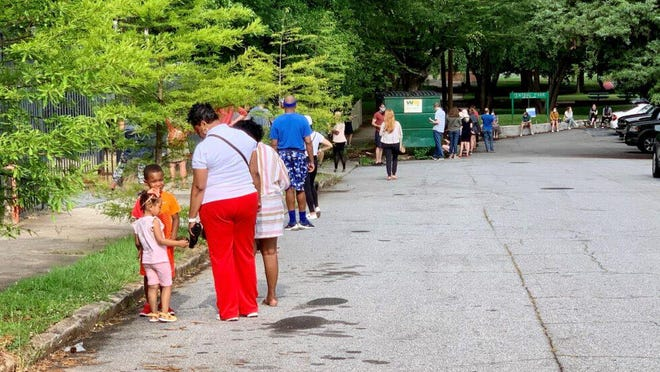 Voters wait in a long line at the Central Park polling place in Atlanta on Primary Election Day, June 9, 2020.