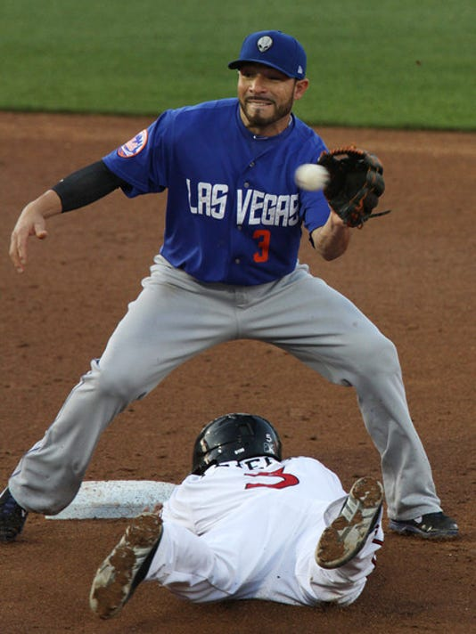 El Paso's Jace Peterson slides beneath Las Vegas shortstop Omar Quintanilla Thursday. Peterson was safe.