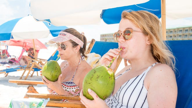 Lorri Wickam, left, and her daughter Mallory Wickam, of Cleveland, Tennessee, enjoy drinking fresh coconut water from Florida Coconuts while sitting along Pensacola Beach on Wednesday, May 30, 2018.