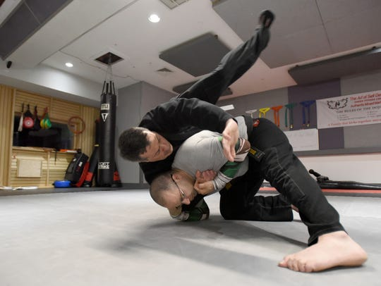 Mahmoud Elayan, left and Sgt. Mark Tagliareni of the Wyckoff Police Department, practice self defense moves at The Art of Self Defense gym in Elmwood Park.