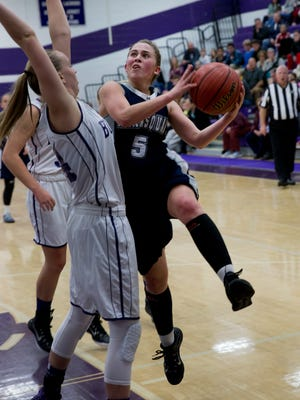 Manasquan's Addie Masonius goes high as she works to shoot over Rumson's Hannah Scanlan during first half action. Manasquan Girls Basketball vs Rumson-Fair Haven in Rumson, NJ on 112/18/15.