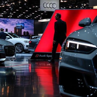 People walk through the Audi display on Monday, Jan.
