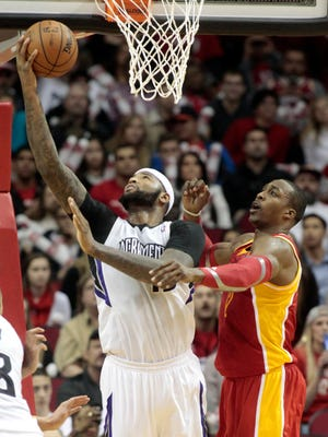 Sacramento Kings center DeMarcus Cousins, left, lays the ball up over Houston Rockets center Dwight Howard during the fourth period of an NBA basketball game, Tuesday, Dec. 31, 2013, in Houston.