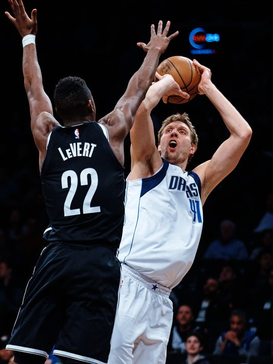 Dallas Mavericks' Dirk Nowitzki (41) shoots next to Brooklyn Nets' Caris Levert (22) during the first half of an NBA basketball game, Saturday, March 17, 2018, in New York. (AP Photo/Andres Kudacki)