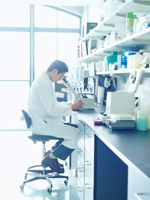 Scientist looking into microscope in research lab, side view