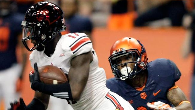 Syracuse?s Corey Winfield, right, tackles Louisville?s James Quick, left, in the first quarter of an NCAA college football game in Syracuse, N.Y., Friday, Oct. 3, 2014. (AP Photo/Nick Lisi)