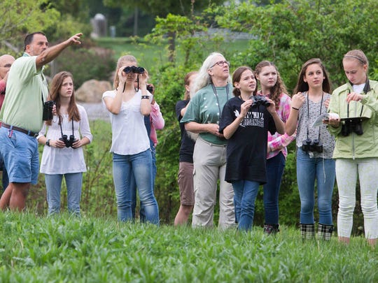 Avid bird watcher Hand Davis (left) points out a bird to the seventh grade science students. Karen Barker's science students at Tatnall School count and monitor bird populations on their campus.