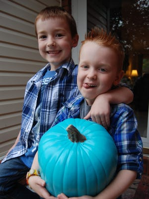 Logan and Luke Metdepenningen put out a teal pumpkin to let people know they hand out non-food treats. Luke, with the pumpkin, has food allergies.