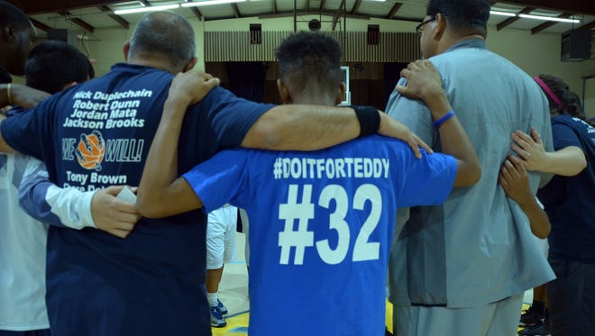 Players and coaches from both First Baptist and Holy Family stand arm in arm for a moment of prayer Tuesday, Dec. 15, when the two teams met again on the court since the untimely death of Teddy Daigle, 14, former Holy Family Catholic player.