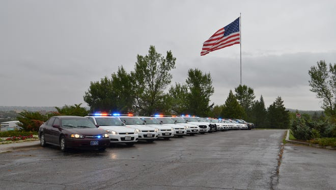 A line of Great Falls Police officers and Cascade County sheriff's deputies parked near the Law Enforcement Memorial on Flag Hill activate their lights as a tribute to a Texas deputy who was killed while on duty last August.