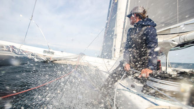 Arete crew member Don Massey gets sprayed by water over the bow during the Port Huron-to-Mackinac Island Sailboat Race.