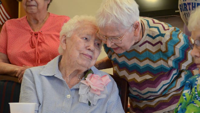Mabel Walker, left, gets a 'Happy Birthday' from Duella Olson at Walker's 100th birthday party Thursday at The Lodge in Great Falls.