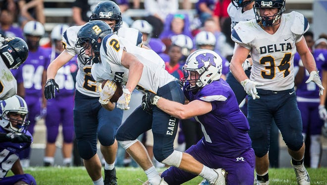 Delta's Wesley Stitt tries to avoid the grasp of Central's Andrew Abbott at Central Friday, Aug. 17, 2018.