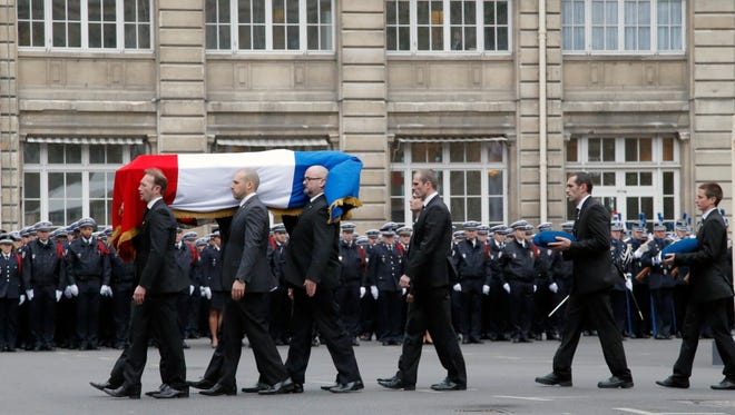 French police officers carry the coffin of police officer Franck Brinsolaro, killed at Charlie Hebdo during a ceremony to pay tribute to the three police officers killed in the attacks, in Paris, France, Tuesday, Jan. 13, 2015.