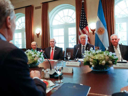 President Donald Trump, accompanied by, from left, Commerce Secretary Wilbur Ross, Vice President Mike Pence, and Secretary of State Rex Tillerson, listens to remarks from Argentine President Mauricio Macri, left, during a luncheon in the Cabinet Room of the White House in Washington, Thursday, April 27, 2017.