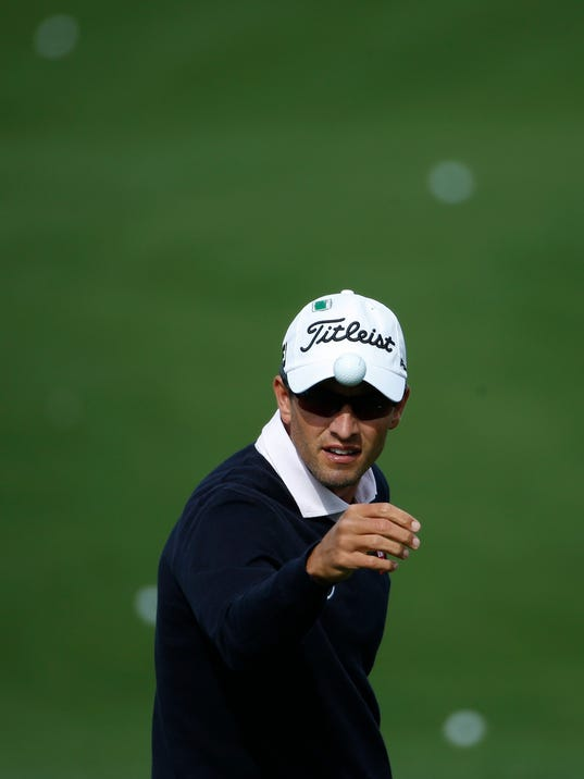 Adam Scott, of Australia, catches a golf ball from his caddie on the driving range during a practice round for the Masters golf tournament Tuesday, April 8, 2014, in Augusta, Ga. (AP Photo/Matt Slocum)
