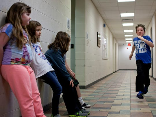 Payton Gurnsey, 10, runs as others do wall sits during Fitness for Kids Thursday at the YMCA of the Blue Water Area.