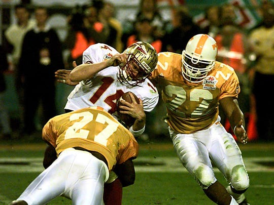 Tennessee's Al Wilson (27) sacks FSU quarterback Marcus Outzen (14) during the third quarter of the Fiesta Bowl on Jan. 4, 1999. Coming up to help at right is Corey Terry (22).