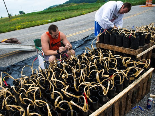 Zambelli Fireworks employees Tyler Brown, left, and