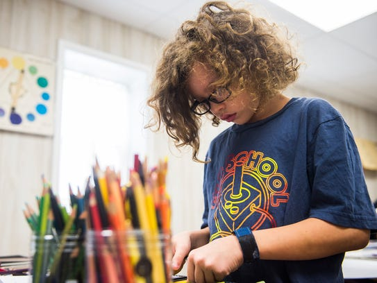 Student Jackson Corbin selects colored pencils for