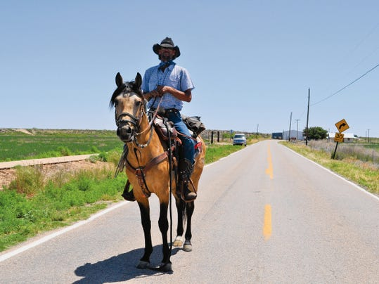 JESSICA ONSUREZ CURRENT-ARGUS   Charlie Kitchens and his buckskin, Bubba, travel down State Road 216 just outside of Carlsbad.   Kitchens left Grandfalls-Royalty, Texas 12 days ago and area headed on a 1,200 mile hourney to Livingston, Mon. where Kitchens said he wants to deposit his father's ashes by the Yellowstone River.   Kitchen's father, James Romer, was a Navy Veteran of the Vietnam War and Kitchens said he is dedicating this journey to him and the other American veterans of war.