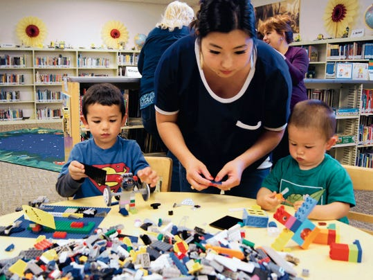 Four-year-old Caden Clark, left, and his little brother, 18-months-old Kai, are helped by their mother Mimi Clark as they play with the Legos at the Lego Club on Wednesday at the Silver City Public Library. The Lego Club meets on Wednesdays at 4 p.m. and is a free event.  Randal Seyler - Sun-News