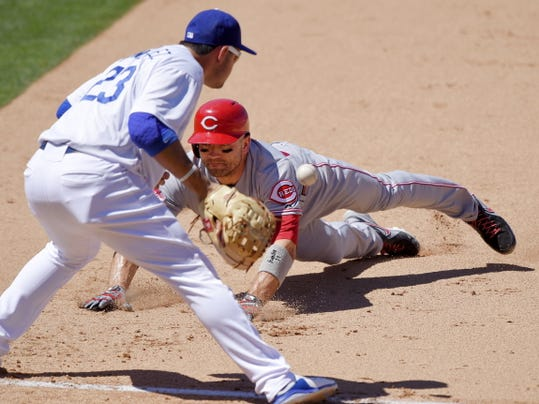 Cincinnati Reds' Joey Votto, right, dives back to first after hitting a single as Los Angeles Dodgers first baseman Adrian Gonzalez awaits the ball from the outfield during the sixth inning of a baseball game, Sunday, Aug. 16, 2015, in Los Angeles. (AP Photo/Mark J. Terrill)