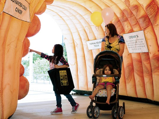 A family walks through New Mexico State University's colon health exhibit at a recent Health and Fitness Expo at the Las Cruces Convention Center. The annual event offers a variety of exhibits, seminars, demonstrations and information on fitness and preventative health care.