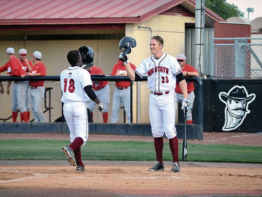 Jett Loe/Sun-News   Daniel Johnson is congratulated by New Mexico State teammate Joseph Koerper after Johnson hit his first home run of the season against New Mexico at Presley Askew Field on Tuesday.