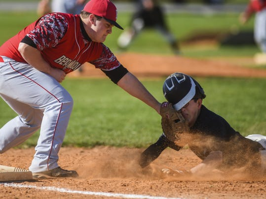 Delone Catholic's Joe Ames, right, takes a glove to the face from Bermudian Springs first baseman Aaron Rebert, who records the out on a pick-off attempt during a game in April.
