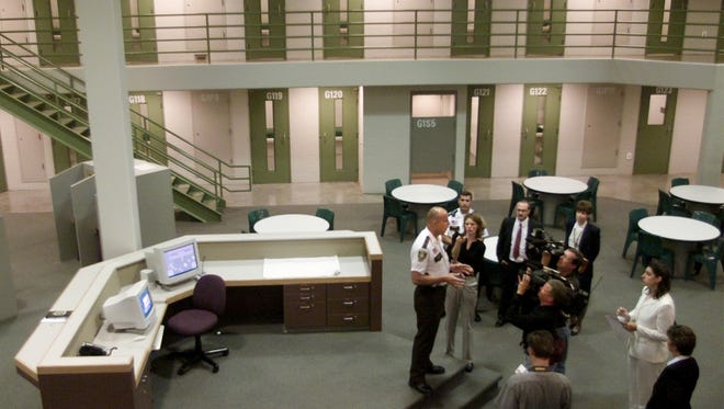 In this July 2000 file photo, then-Sherburne County Sheriff Bruce Anderson leads a group of reporters and photographers through a pod designed to hold primarily pre-sentenced federal prisoners for the U.S. Marshals Service in the expanded, 358-bed Sherburne County Jail in Elk River.