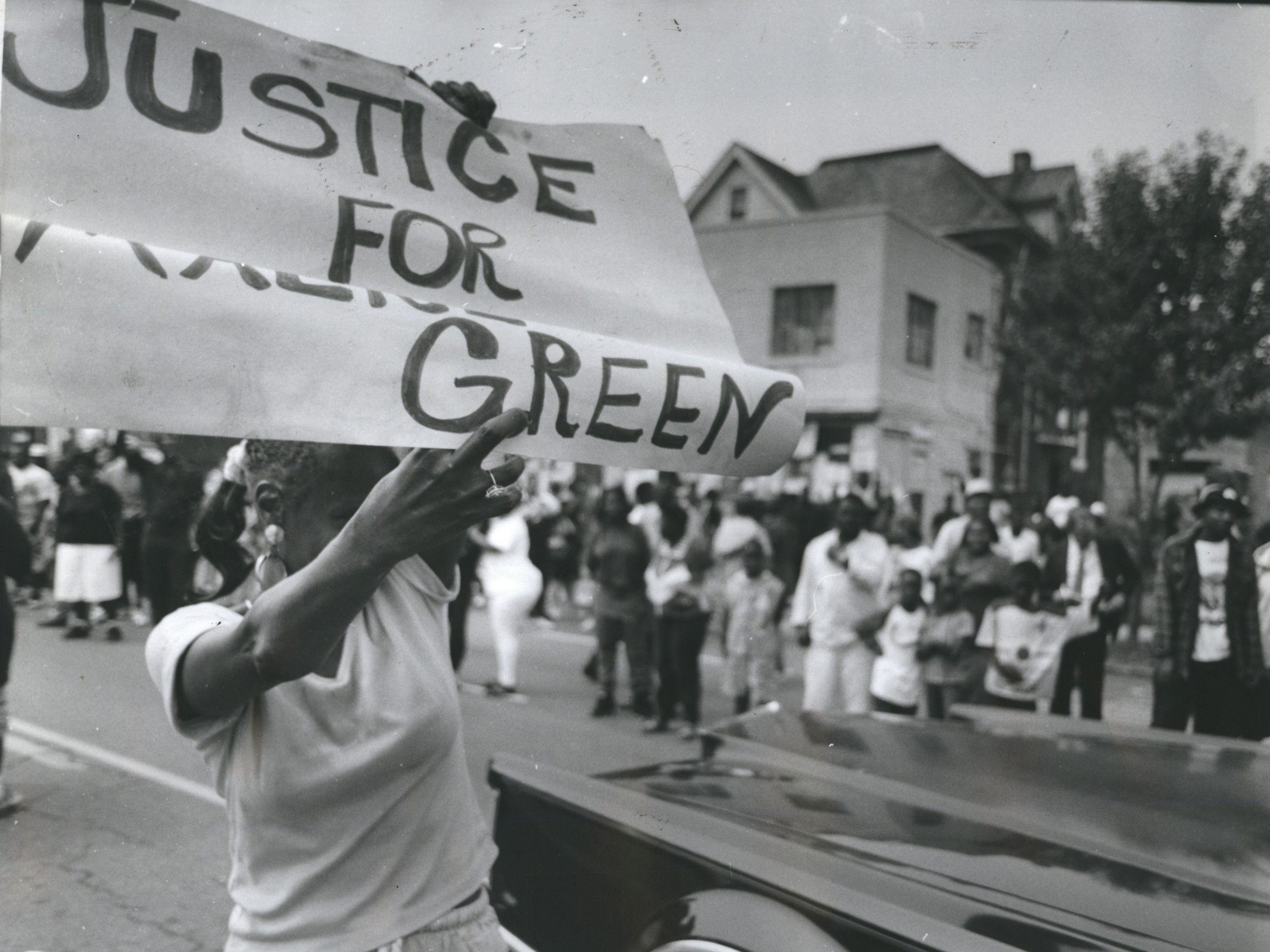 "A women waves a sign that says ""Justice for Malice"