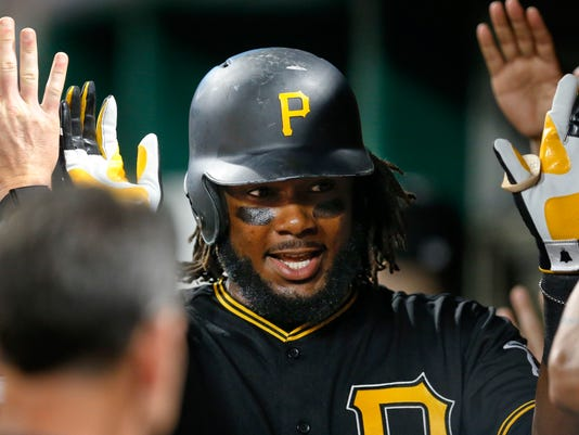FILE - In this Sept. 27, 2017, file photo, Pittsburgh Pirates' Josh Bell is congratulated in the dugout by teammates after hitting a two-run home run in the third inning of a baseball game against the Baltimore Orioles, in Pittsburgh. Bell's vibrant rookie season was a flash of hope in an otherwise dismal 2017 for the Pirates. The first baseman is hoping to prove it wasn't a fluke. (AP Photo/Keith Srakocic, File)