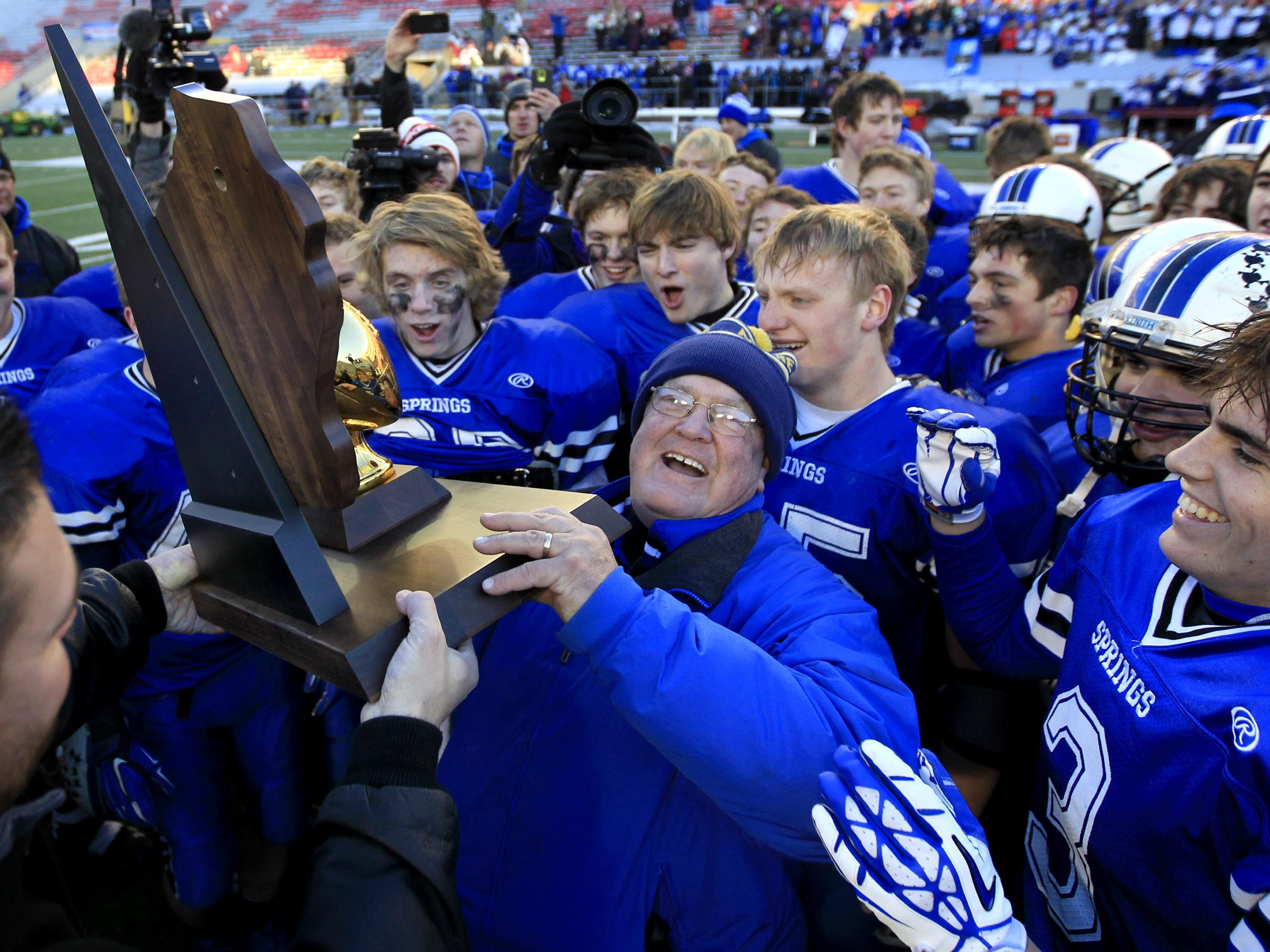 St. Mary's Springs head coach Bob Hyland accepts the championship trophy after the Ledgers' 37-21 victory over Darlington last year in Madison.