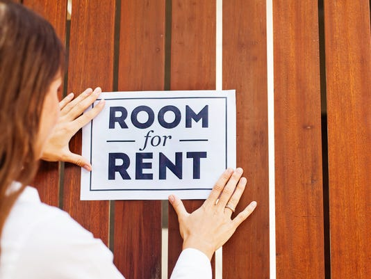 "house owner attaching ""Room for rent"" sign on a wall"