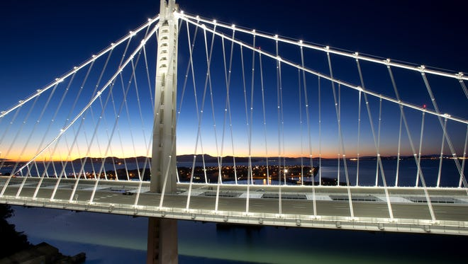 In a handout photo provided by the Bay Area Toll Authority, LED lights illuminate the San Francisco-Oakland Bay Bridge's self-anchored suspension last month.