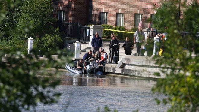 Police and fire department scuba teams launch from an area near Brooks Crossing Apartments.