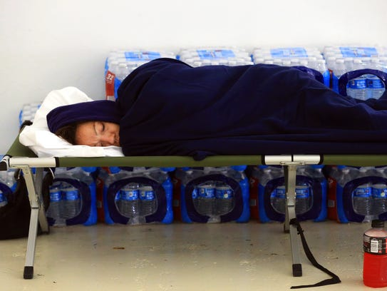 A woman sleeps on a cot after she evacuated to a shelter