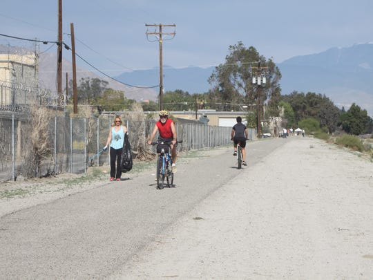 A volunteer cleans up a bicycle path in Cathedral City that will soon be part of the proposed CV Link.