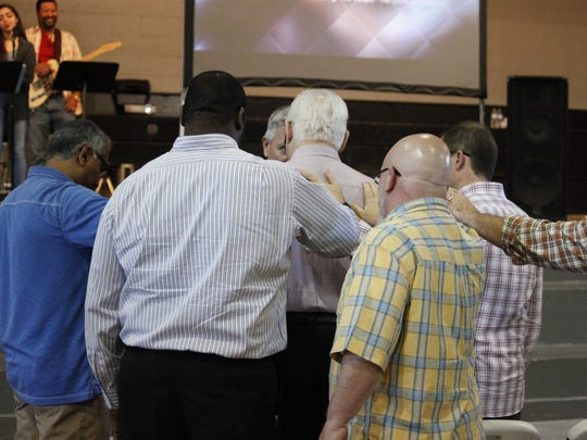 People at New Life Church pray during Sunday's service. The church changed its name  one year ago.