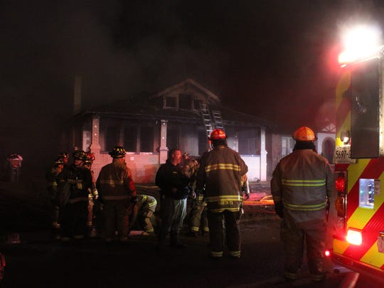 Firefighters stand by the building after extinguishing a fire that claimed two lives at a home on the 300 block of Main Street in Martin late Sunday night.