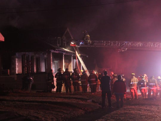 A firefighter climbs to the second floor of a home on the 300 block of Main Street in Martin after several fire departments worked to extinguish a fire that claimed two lives late Sunday night.