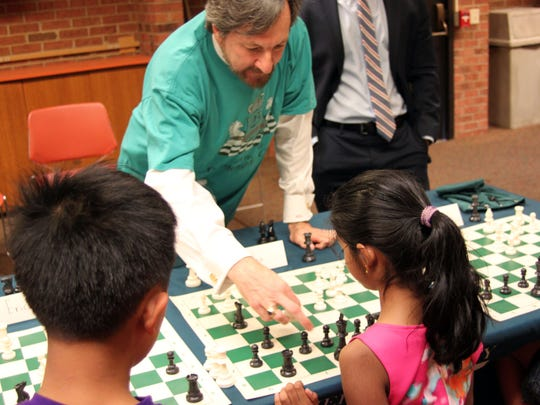 On June 29 at SCLSNJ's Bridgewater Library branch, Freeholder Brian Levine challenged 10 Somerset County students to a simultaneous chess tournament. Each child battled valiantly, but Levine, and his lucky chess T-shirt, was able to defeat each challenger. The games lasted almost three hours. Levine graciously donated six professional chess sets to the Library, and the system hopes to host a second tournament in the near future. Here, Levine ponders his next move against  Sraddha Pedaprolu, 8, of Bridgewater.