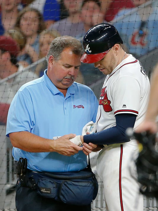 Atlanta Braves first baseman Freddie Freeman (5) has his hand examined by trainer Jim Lovell after he was hit by a pitch from Toronto Blue Jays relief pitcher Aaron Loup (62) in the fifth inning of a baseball game, Wednesday, May 17, 2017, in Atlanta. Freeman left the game. (AP Photo/John Bazemore)