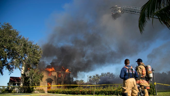 Iona-McGregor firefighters watch as a house burns on Sunday in Fort Myers as a part of a training exercise.