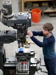 North Kitsap High School engineering student Bradley Barrett uses a drill press to make a spindle holder.
