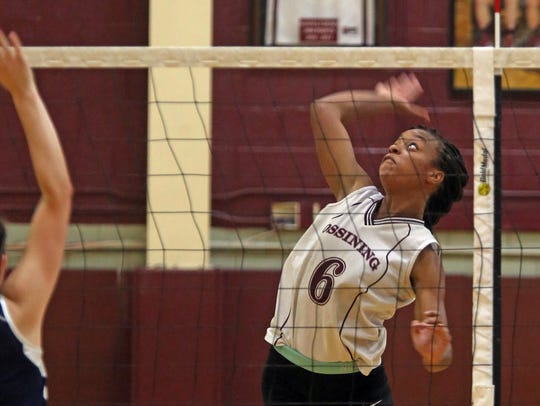 Ossining's Mychael Vernon (6) spikes the ball during