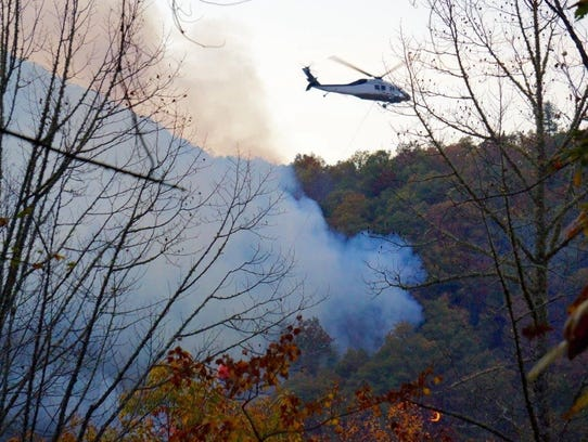 A helicopter drops retardant on the Moses Creek Fire