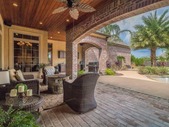 The outdoor space includes a full outdoor kitchen.