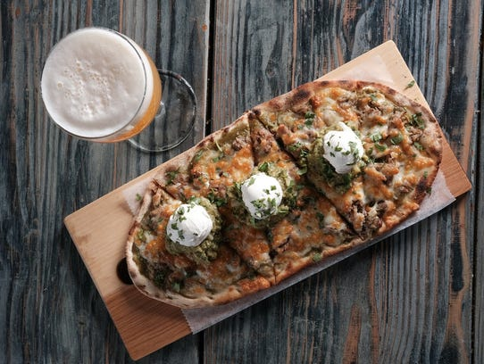 The Carnitas pizza includes seasoned beer-braised pork, tomatillo salsa, jack cheese, guacamole and sour cream.